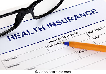 Health insurance claim form with glasses and ballpoint pen.