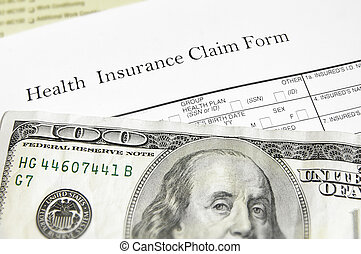 health insurance claim form and cash, closeup