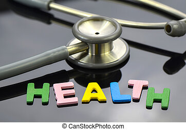 HEALTH letter with stethoscope on dark background.