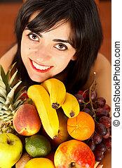 Kind brunette girl embracing a dish full of fruits enjoying healthy life.