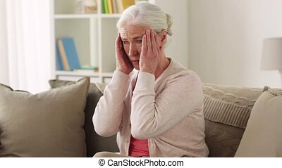 senior woman suffering from headache - health, old age and...