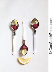 Health or detox diet food idea, spoon with lemon and raspberrieson.