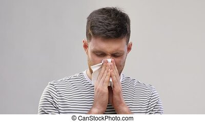 sick young man with paper tissue blowing nose - health, ...
