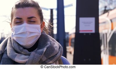 woman in protective face mask at railway station - health ...