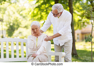 senior woman suffering from headache outdoors
