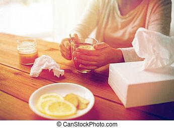 ill woman drinking tea with lemon and honey