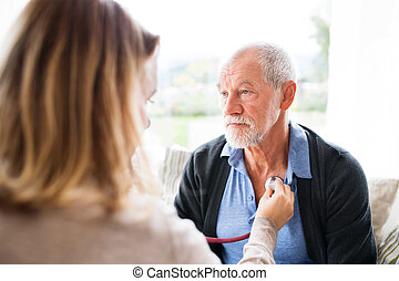 Health visitor and a senior man during home visit.