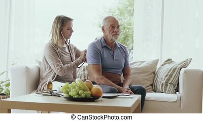 Health visitor and a senior man during home visit. A female...