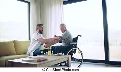 Health visitor and a senior man in wheelchair during home visit, checking blood pressure. Slow motion.