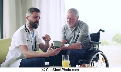 Health visitor and a senior man in wheelchair during home visit.