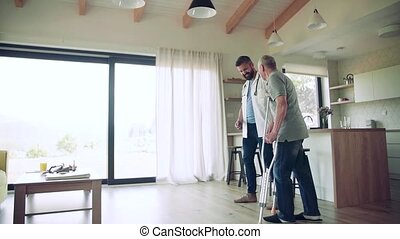 Health visitor and a senior man with crutches during home visit, walking.