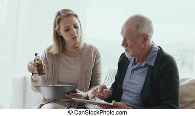 Health visitor and a senior man with tablet during home...