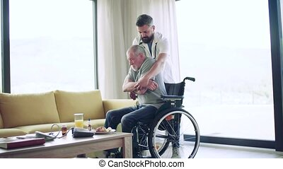 Health visitor and a senior man with wheelchair during home visit.