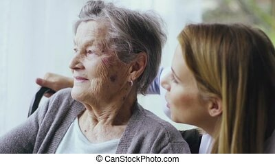 Health visitor and a senior woman during home visit. A nurse...