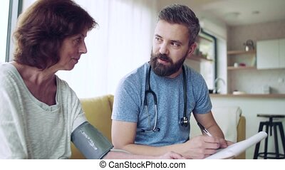 Health visitor and a senior woman during home visit, checking blood pressure.