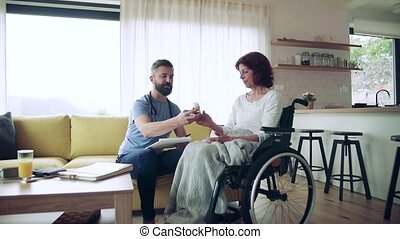 Health visitor and a senior woman in wheelchair during home visit, talking about taking medication. Slow motion.