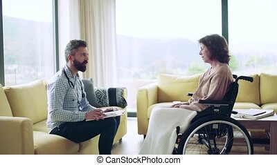 Health visitor and a senior woman in wheelchair during home visit.