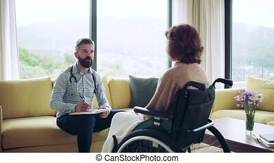 Health visitor and a senior woman in wheelchair during home visit, talking. Slow motion.