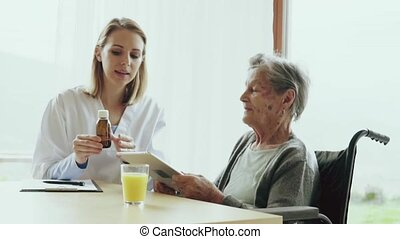 Health visitor and a senior woman with tablet. - Health...