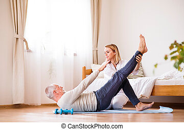 Health visitor and senior man during home visit. - Health...