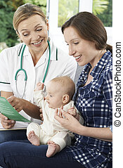 Health Visitor Discussing Leaflet With Mother Holding Baby At Home