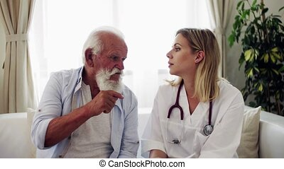 Health visitor with stethoscope and a senior man at home,...