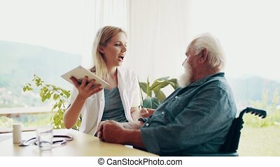 Health visitor with tablet and a senior man in wheelchair at home, talking.