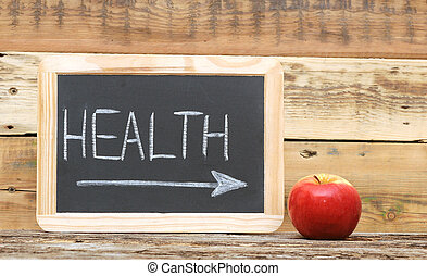 """""""health"""" word on blackboard with arrow show on red apple"""