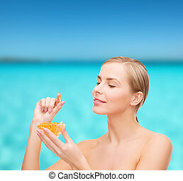 healthcare and beauty concept - lovely woman with omega 3 vitamins