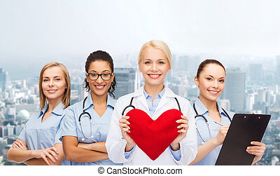 smiling female doctor and nurses with red heart