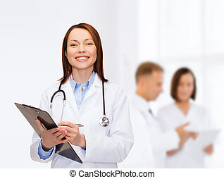 smiling female doctor with clipboard - healthcare and ...
