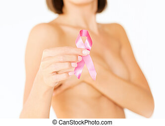 hand holding pink breast cancer awareness ribbon -...