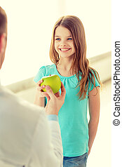 male doctor giving an apple to smiling little girl