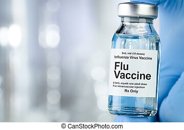 Healthcare concept with a hand in blue medical gloves holding Flu, Influenza, vaccine vial