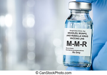 Healthcare concept with a hand in blue medical gloves holding MMR, measles, mumps, and rubella, vaccine vial