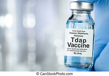 Healthcare concept with a hand in blue medical gloves holding Tap, tetanus, diptheria, and pertussis, vaccine vial
