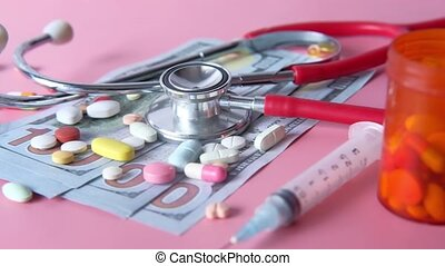 Healthcare cost concept with us dollar , container and pills on table .