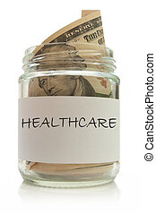Healthcare fund - Jar full of dollar notes over a white...