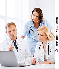 doctors looking at laptop on meeting - healthcare, medical ...