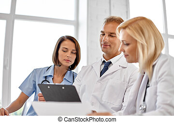 group of doctors with clipboard at hospital