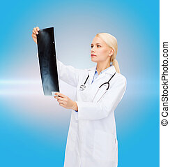 serious female doctor looking at x-ray - healthcare,...