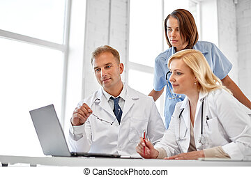group of doctors with laptop computer at hospital