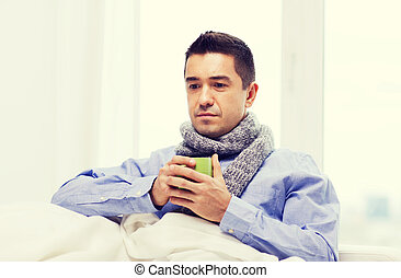 ill man with flu drinking hot tea from cup at home