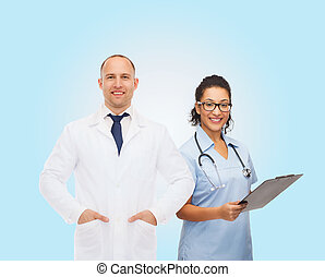 smiling doctors with clipboard and stethoscopes -...