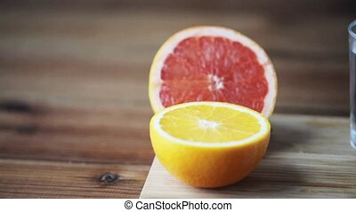orange, grapefruit and glass of water with pills -...