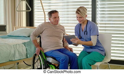 Healthcare worker and senior patient in wheelchair in hospital, talking.