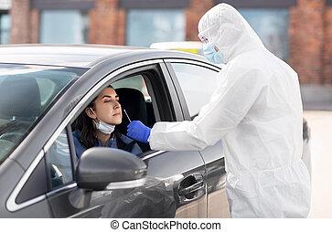 healthcare worker making coronavirus test at car - medicine...