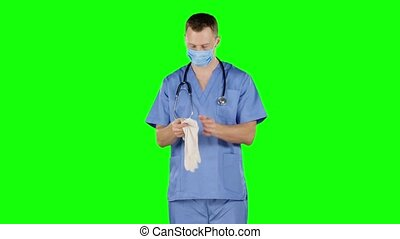 Healthcare worker putting on medical gloves. Green screen