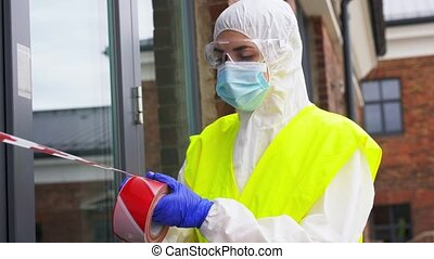quarantine and pandemic concept - healthcare worker in protective gear, medical mask, gloves and goggles enclosing building with caution tape outdoors