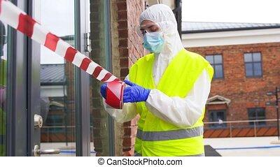 healthcare worker sealing door with caution tape - ...